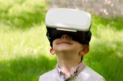 Garçon dans un casque de réalité virtuelle sur un fond d'herbe verte Photographie stock