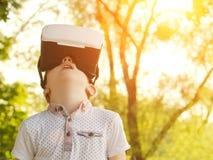 Garçon dans un casque de réalité virtuelle sur un fond de la tonalité verte de forêt Photos stock
