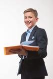 Garçon dans un costume avec un carnet à disposition Images stock