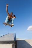 Garçon dans un saut sur une planche à roulettes Photos stock