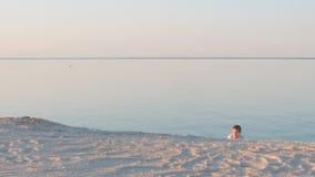 Garçon dans une chemise blanche sur une plage d'été au coucher du soleil clips vidéos