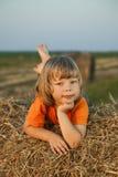 Garçon dans une meule de foin dans le domaine Photographie stock libre de droits