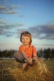 Garçon dans une meule de foin dans le domaine Photo stock
