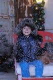 Garçon dans une veste et un chapeau de fourrure dans Noël avec des flocons de neige Photos stock