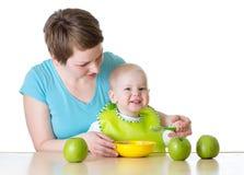 Garçon de alimentation d'enfant de mère avec la cuillère d'isolement sur le blanc photo stock