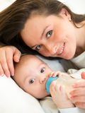 Garçon de alimentation d'enfant de mère avec une bouteille à lait à la maison Photo libre de droits