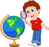 Garçon de bande dessinée à l'aide de la loupe regardant le globe Images stock