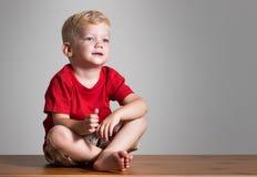 Garçon de beauté s'asseyant sur une table Photo stock