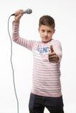 Garçon de brune de chanteur dans un pullover rose avec un microphone Images libres de droits
