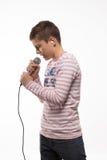Garçon de brune de chanteur dans un pullover rose avec un microphone et des écouteurs Image libre de droits