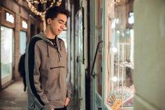 Garçon de brune regardant le magasin la nuit images stock