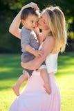 Garçon de caresse d'enfant en bas âge de mère tout en se tenant dehors Photo libre de droits