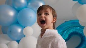 Garçon de deux ans dans une chemise blanche se reposant à la maison dans des ballons bleus banque de vidéos