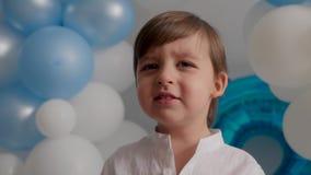 Garçon de deux ans dans une chemise blanche se reposant à la maison dans des ballons bleus clips vidéos