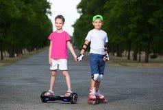 Garçon de deux enfants sur les raies et la fille de rouleau sur le scooter de auto-équilibrage enveloppé Images stock
