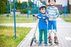 Garçon de deux enfants sur les raies de rouleau et son frère d'enfant de mêmes parents sur le scooter image stock