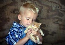 Garçon de ferme tenant un chaton et savourant l'amour Photographie stock libre de droits