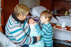Garçon de grand-mère et d'enfant tenant l'petit-enfant nouveau-né de bébé sur des bras Photographie stock libre de droits