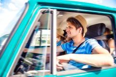 Garçon de hippie conduisant un vieux campervan avec des adolescents, promenade en voiture Photo stock
