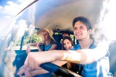 Garçon de hippie conduisant un vieux campervan avec des adolescents, promenade en voiture Image stock