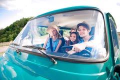 Garçon de hippie conduisant un vieux campervan avec des adolescents, promenade en voiture Image libre de droits