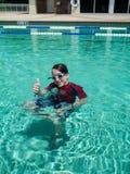 Garçon de jeune adolescent donnant des pouces dans la piscine Photographie stock libre de droits