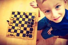 Garçon de jeune garçon jouant des échecs ayant l'amusement Photos libres de droits