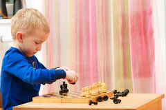 Garçon de jeune garçon jouant des échecs ayant l'amusement Photo stock