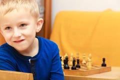 Garçon de jeune garçon jouant des échecs ayant l'amusement Image libre de droits