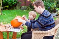Garçon de jeune homme et d'enfant en bas âge effectuant le potiron de veille de la toussaint Photo stock