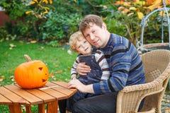 Garçon de jeune homme et d'enfant en bas âge effectuant le potiron de veille de la toussaint Images stock