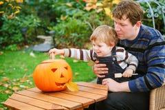 Garçon de jeune homme et d'enfant en bas âge effectuant le potiron de veille de la toussaint Image stock