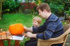 Garçon de jeune homme et d'enfant en bas âge effectuant le potiron de veille de la toussaint Photographie stock libre de droits