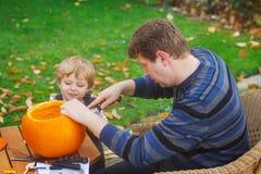 Garçon de jeune homme et d'enfant en bas âge effectuant le potiron de veille de la toussaint Photographie stock