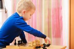 Garçon de jeune garçon jouant des échecs ayant l'amusement Image stock