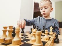 Garçon de jeune garçon jouant des échecs ayant l'amusement Photographie stock libre de droits