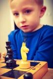 Garçon de jeune garçon jouant des échecs ayant l'amusement photos stock