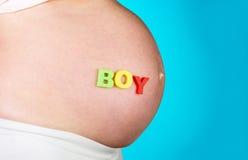 Garçon de légende sur la femme enceinte de ventre Photos stock