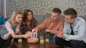Garçon de l'adolescence allumant une bougie d'anniversaire sur le gâteau avec des amis à la maison Photo stock