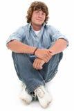 Garçon de l'adolescence attirant de seize ans s'asseyant sur l'étage Photographie stock