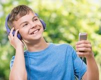 Garçon de l'adolescence avec des écouteurs Images libres de droits