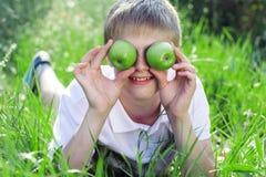 Garçon de l'adolescence avec la pyramide des pommes vertes se trouvant dessus photo stock