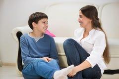 Garçon de l'adolescence avec sa jeune mère à la maison Image stock