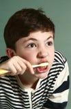 Garçon de l'adolescence balayant son teath Image stock