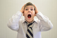 Garçon de l'adolescence criant tenant ses mains derrière la tête Photo libre de droits