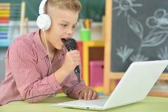 Garçon de l'adolescence dans des écouteurs chantant le karaoke photo stock
