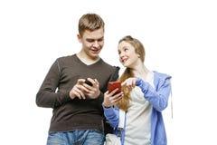 Garçon de l'adolescence et fille se tenant avec des téléphones portables Images stock