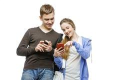 Garçon de l'adolescence et fille se tenant avec des téléphones portables Image libre de droits