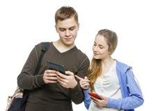 Garçon de l'adolescence et fille se tenant avec des téléphones portables Images libres de droits
