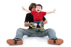 Garçon de l'adolescence et garçon d'enfant en bas âge jouant ainsi que la planche à roulettes Photos libres de droits